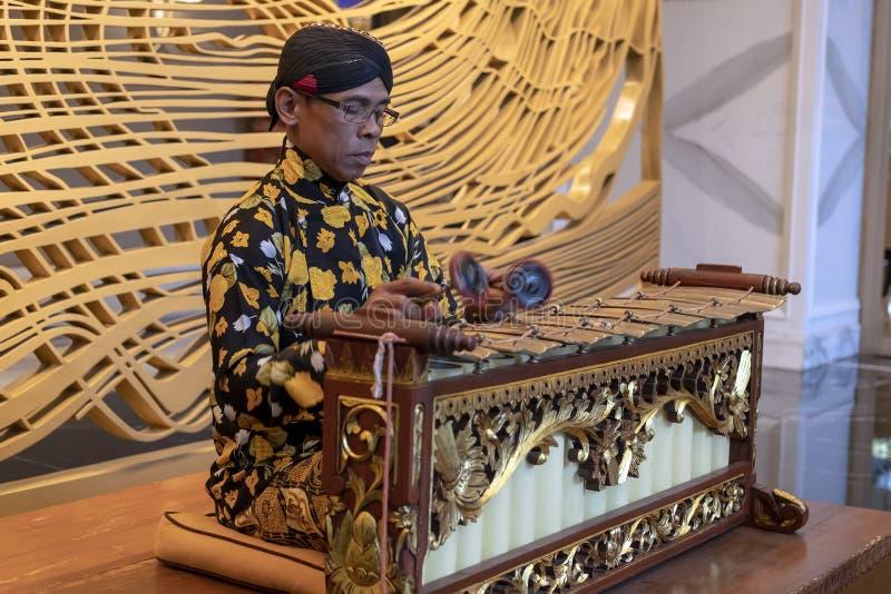 Un hombre Javanese que juega el slenthem, un instrumento de música tradicional Javanese fotos de archivo
