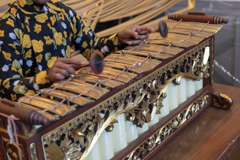Un hombre Javanese que juega el slenthem, un instrumento de música tradicional Javanese imagenes de archivo