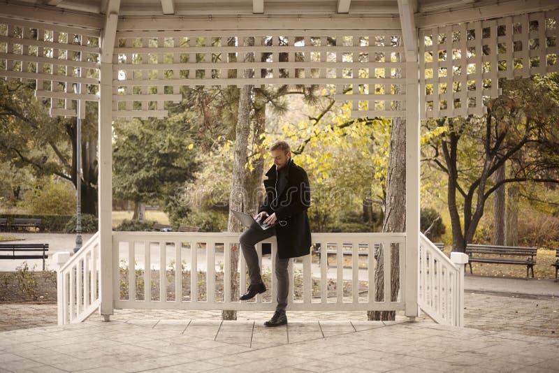 Un hombre joven, 20-29 a?os, sent?ndose en la cerca al aire libre en parque, elaboraci?n de la oficina, en parque p?blico en su o imagen de archivo