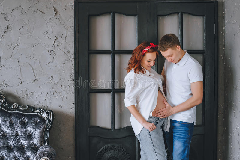 Un hombre joven acertado y una mujer embarazada hermosa joven Miramos uno a y abrazamos el midsection Sesión fotográfica fotografía de archivo