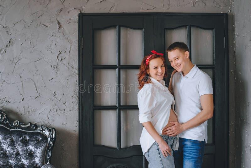 Un hombre joven acertado y una mujer embarazada hermosa joven Miramos uno a y abrazamos el midsection Una mujer adentro fotos de archivo libres de regalías