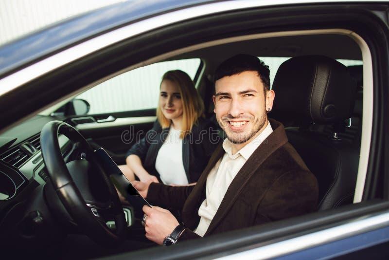 Un hombre joven alquila un coche El empleado del centro del distribuidor autorizado muestra documentos en el coche foto de archivo