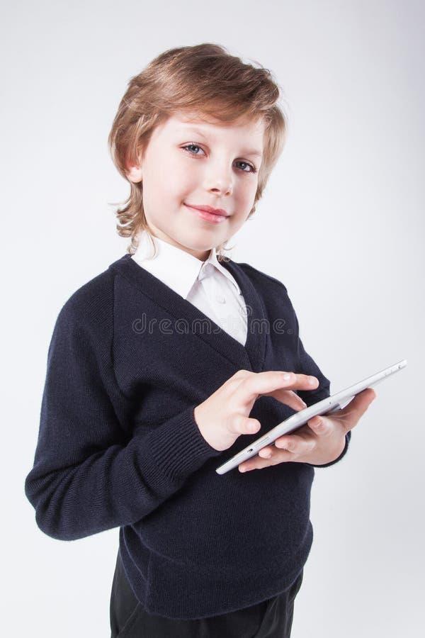 Un hombre joven ambicioso con una sonrisa, celebrando una tableta foto de archivo libre de regalías