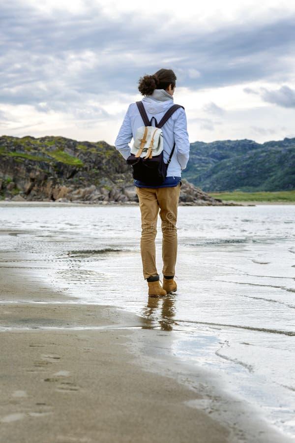 Un hombre joven camina a lo largo de la costa del Mar del Norte frío Visi?n posterior D?a asoleado imagen de archivo libre de regalías