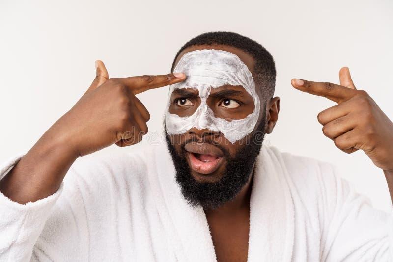 Un hombre joven con la máscara de papel en la cara que parece chocada con una boca abierta, aislada en un fondo blanco foto de archivo libre de regalías