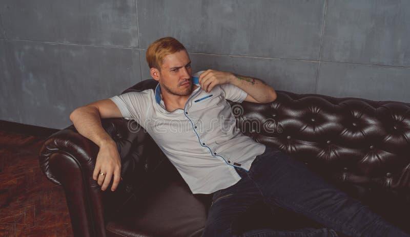 Un hombre joven con un tatuaje en su mano que presenta en un sofá de cuero ropa del estilo de la calle: camisa blanca y vaqueros  imagenes de archivo