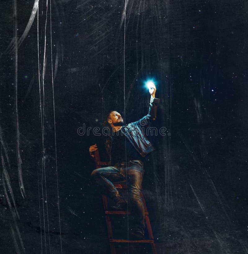 Un hombre joven con una barba en las escaleras sostiene una estrella contra la perspectiva del cielo nocturno con los rasguños Co fotos de archivo libres de regalías