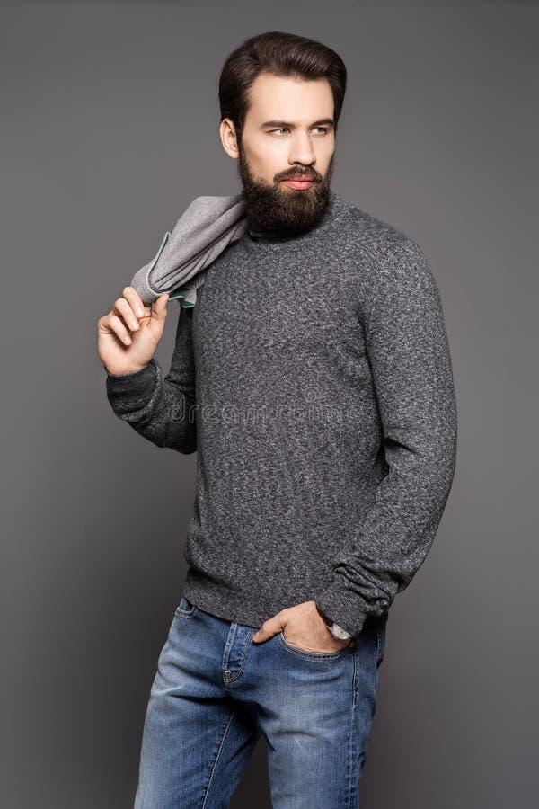 Un hombre joven con una barba, llevando una chaqueta y vaqueros imagen de archivo