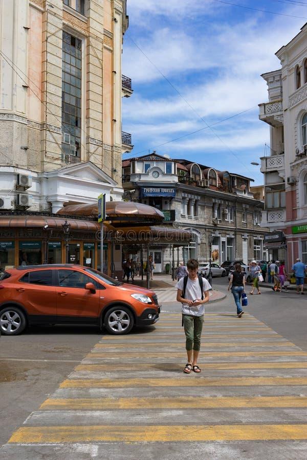 Un hombre joven cruza el camino en la ciudad foto de archivo