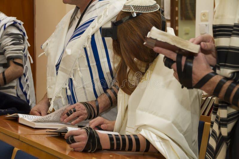 Un hombre joven de rogación con un tefillin en su brazo y cabeza, sosteniendo un libro de la biblia, mientras que lee una rogació imagen de archivo libre de regalías