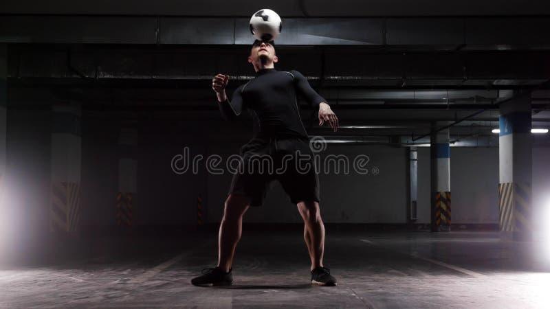Un hombre joven del fútbol que entrena a los trucos básicos con la bola que equilibra la bola en la cabeza fotografía de archivo libre de regalías