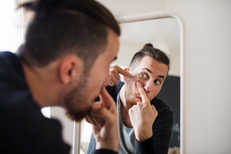 Un hombre joven dentro que mira en el espejo, exprimiendo una espinilla fotografía de archivo libre de regalías