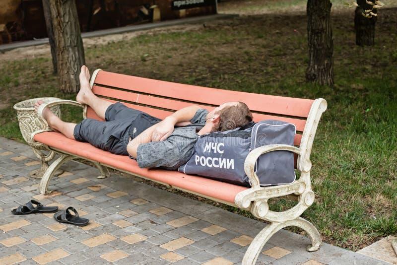 Un hombre joven duerme en un banco en el parque que miente en el bolso con fotografía de archivo