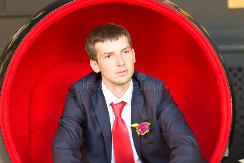 Un hombre joven elegante en la sentada del smoking, mirando lejos de la cámara fotografía de archivo