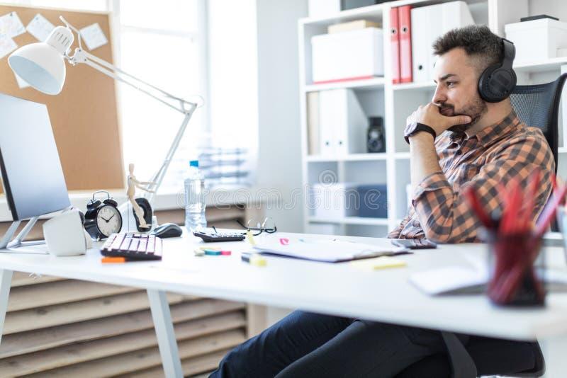 Un hombre joven en auriculares se sienta en una tabla en la oficina y mira el monitor fotos de archivo libres de regalías