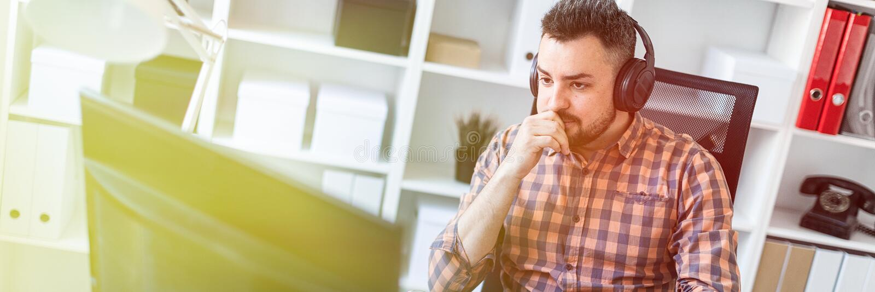 Un hombre joven en auriculares se sienta en una tabla en la oficina y mira el monitor foto de archivo