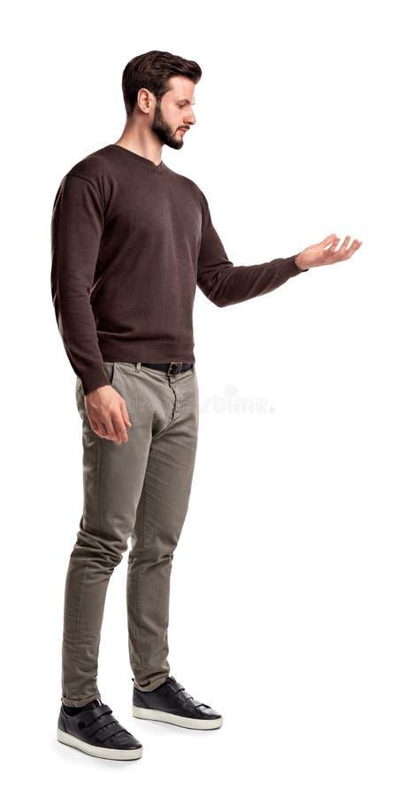 Un hombre joven en casual de moda cierra soportes en una vista lateral y mira una mano dada vuelta encima de como si lleve a cabo imagen de archivo