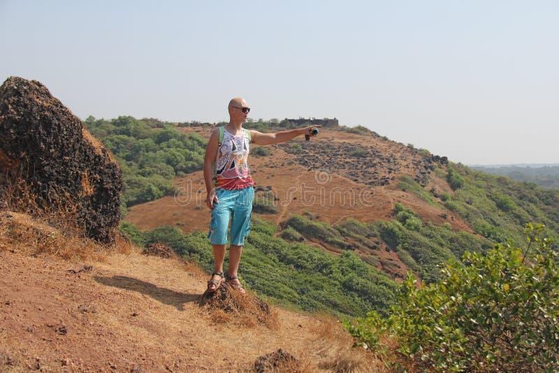 Un hombre joven en gafas de sol en naturaleza está señalando su finger en foto de archivo libre de regalías