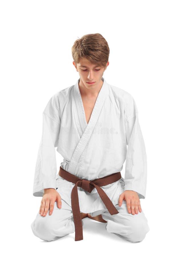 Un hombre joven en un kimono que se sienta en una actitud del loto fotos de archivo