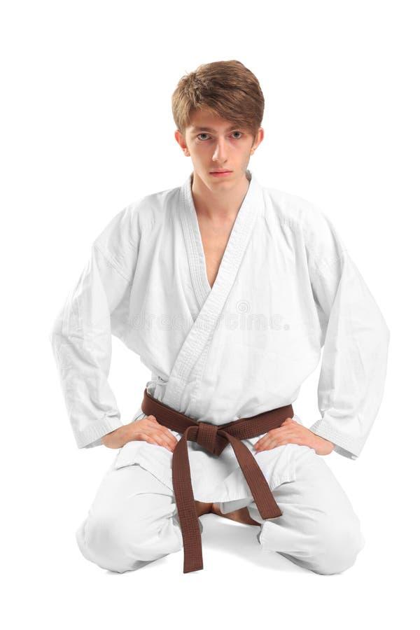 Un hombre joven en un kimono que se sienta en una actitud del loto imagen de archivo