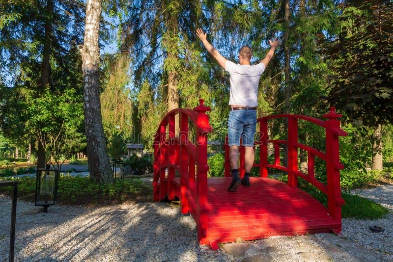 Un hombre joven en pantalones cortos del dril de algodón y una camiseta ligera que caminan con sus manos para arriba en un puente fotografía de archivo