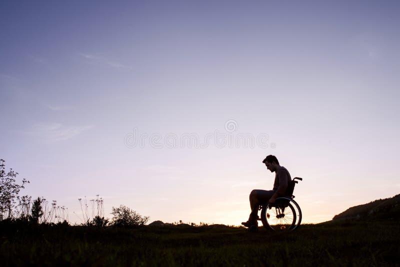 Un hombre joven en silla de ruedas en naturaleza por la tarde fotografía de archivo libre de regalías