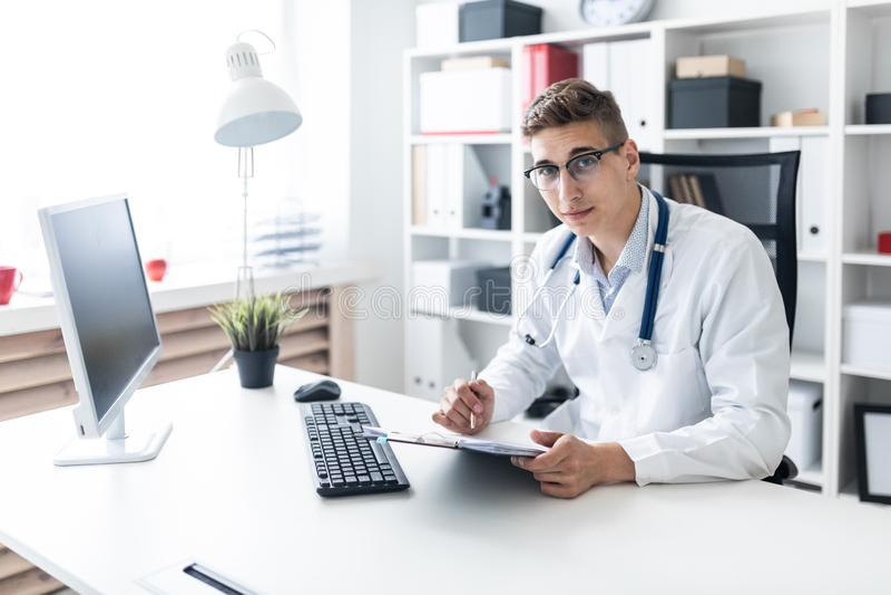 Un hombre joven en un traje blanco que se sienta en una tabla en la oficina Él está sosteniendo una pluma y una tableta con los d fotos de archivo