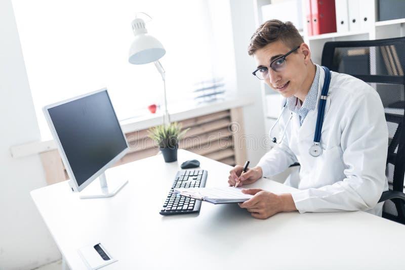 Un hombre joven en un traje blanco que se sienta en una tabla en la oficina Él está sosteniendo una pluma y una tableta con los d fotografía de archivo libre de regalías