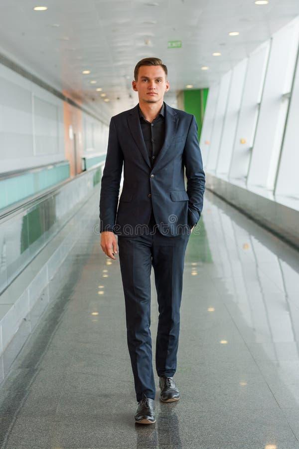 Un hombre joven en un traje está caminando a lo largo del pasillo del aeropuerto fotografía de archivo libre de regalías
