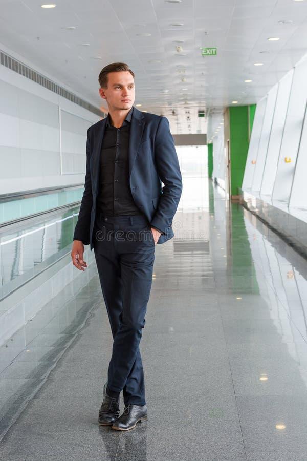 Un hombre joven en un traje se coloca en el aeropuerto cerca de la escalera m?vil y la mirada a la ventana imagen de archivo