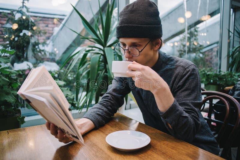 Un hombre joven en un casquillo y una camisa que lee un libro y que bebe el café en un restaurante con el invernadero fotos de archivo