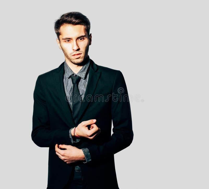 Un hombre joven en un traje de moda que presenta en fondo gris indoor Color caliente imagenes de archivo