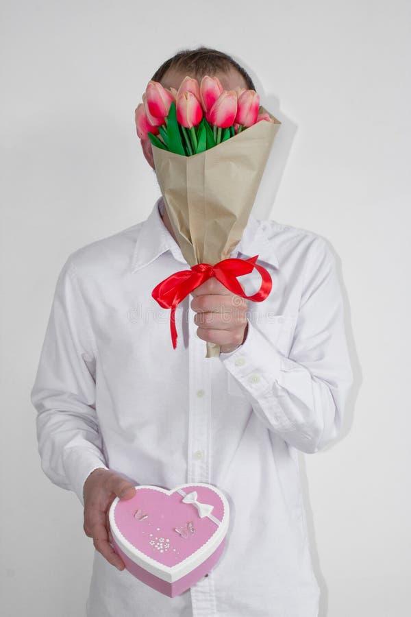 Un hombre joven en una camisa blanca y vaqueros sostiene un ramo de tulipanes cerca de su cara y sostiene una caja de regalo en f fotos de archivo