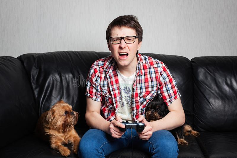 Un hombre joven en una camisa roja y tejanos se sienta en casa y juega a los videojuegos así como su perro Muchacho de griterío d imagen de archivo libre de regalías