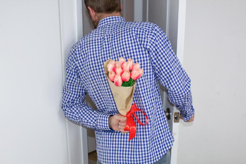 Un hombre joven en una camisa y los vaqueros de tela escocesa azul, refrenando un ramo de tulipanes detrás el suyo, y ojeadas en  fotos de archivo