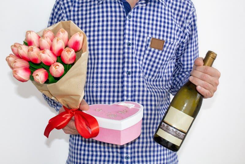 Un hombre joven en una camisa y los vaqueros de tela escocesa azul, sosteniendo un ramo de tulipanes, una caja de regalo en forma fotografía de archivo libre de regalías