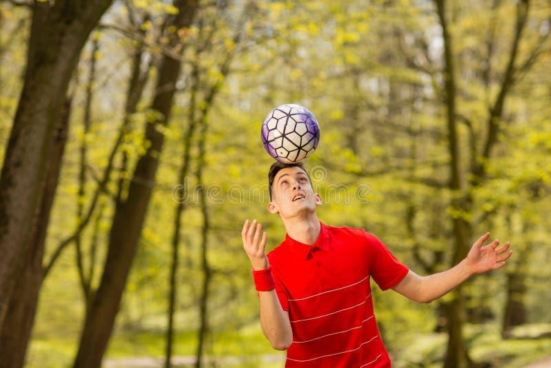 Un hombre joven en una camiseta roja juega con un bal?n de f?tbol en el parque verde Concepto del deporte imagen de archivo