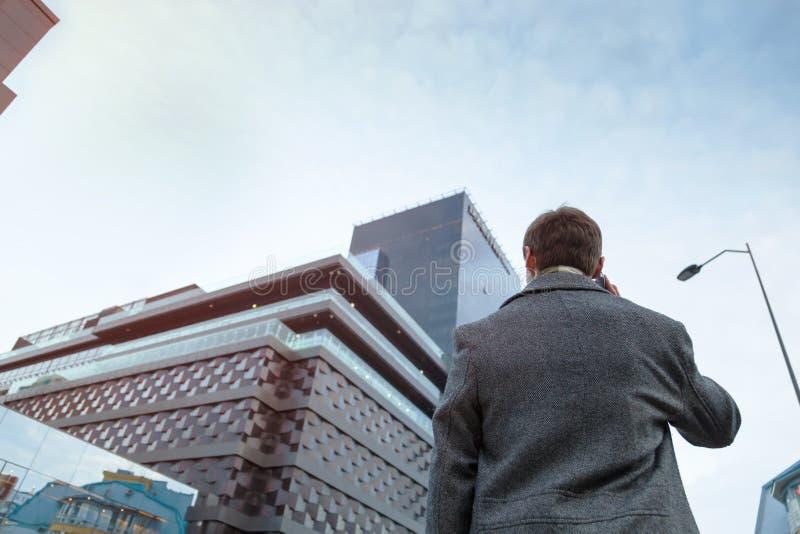 Un hombre joven en una capa hace una llamada de teléfono anónima que se coloca cerca del centro de negocios foto de archivo libre de regalías