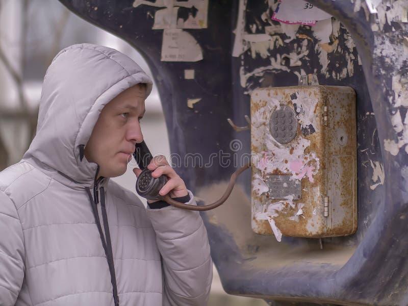 Un hombre joven en una chaqueta con una capilla está hablando con un teléfono público viejo en la calle fotografía de archivo libre de regalías