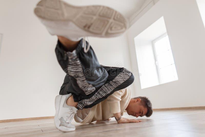 Un hombre joven está bailando danza de rotura en un jersey blanco imagen de archivo libre de regalías