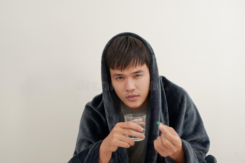 Un hombre joven está enfermo con gripe, miente en casa debajo de una manta, toma una píldora fotografía de archivo
