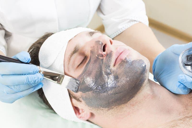Un hombre joven está experimentando un tratamiento de la máscara imagen de archivo