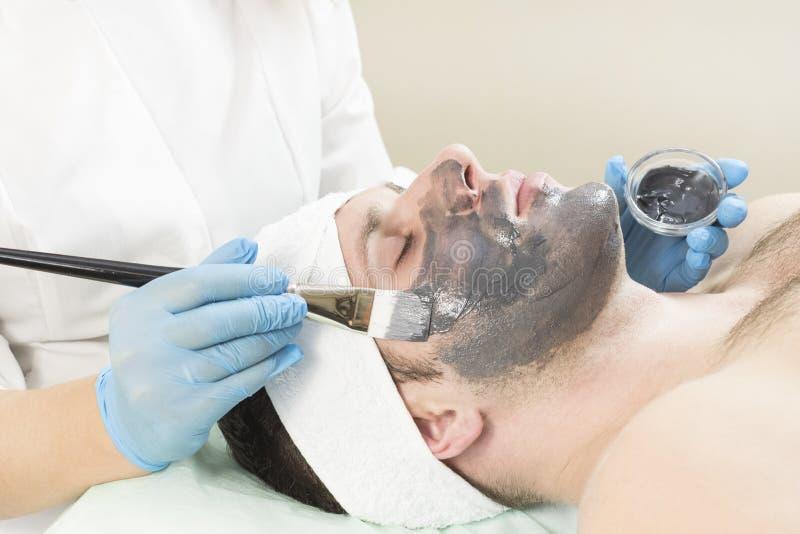 Un hombre joven está experimentando un tratamiento de la máscara imagenes de archivo