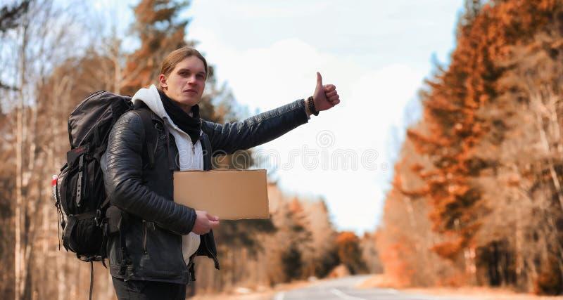 Un hombre joven está haciendo autostop alrededor del país El hombre está intentando foto de archivo