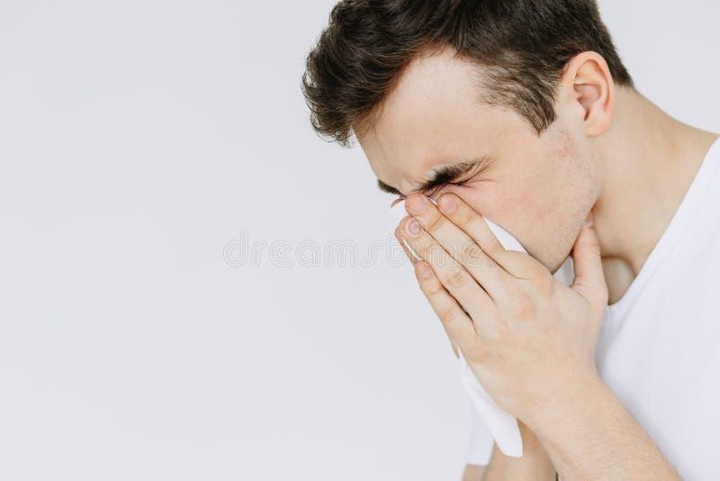 Un hombre joven estornuda en una servilleta Fondo blanco aislado fotos de archivo