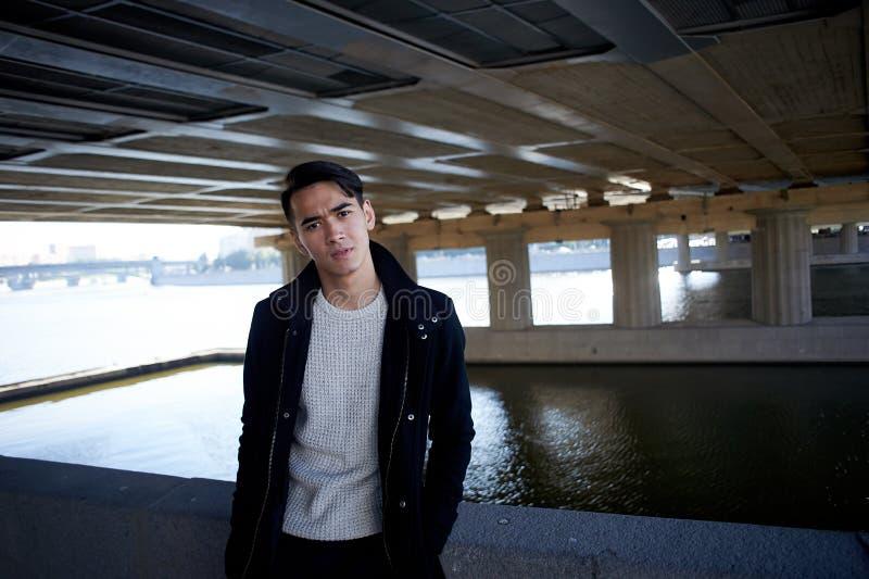 Un hombre joven, fino Con los ojos del pelo oscuro y del marrón Colocándose debajo del puente en el río, mire la cámara gente ade fotos de archivo