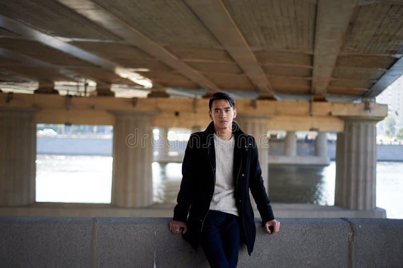 Un hombre joven, fino Con los ojos del pelo oscuro y del marrón Colocándose debajo del puente en el río, mire la cámara gente ade fotos de archivo libres de regalías