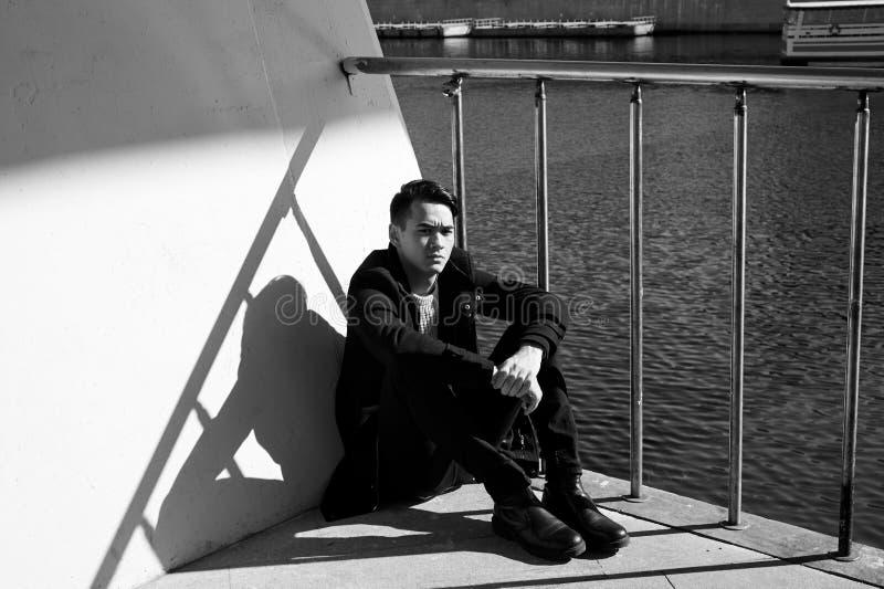 Un hombre joven, fino Con los ojos del pelo oscuro y del marrón El sentarse en los pasos cerca del agua Triste Gente en la ciudad imagen de archivo