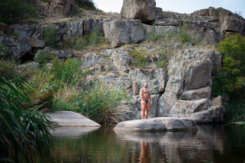 Un hombre joven fuerte se sienta en una roca en el medio del agua en verano Natación del verano en el río entre rocas fotos de archivo libres de regalías