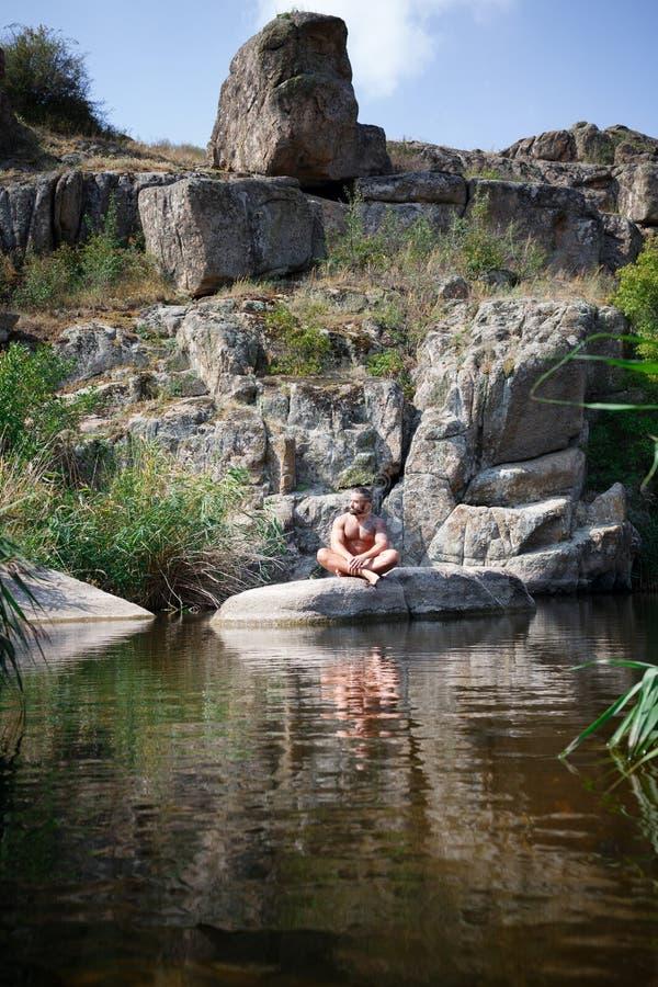 Un hombre joven fuerte se sienta en una roca en el medio del agua en verano Natación del verano en el río entre rocas foto de archivo